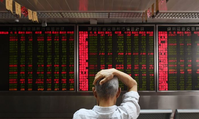 A man checks stock-price movements at a securities company in Beijing on July 4, 2018. (Greg Baker/AFP/Getty Images)