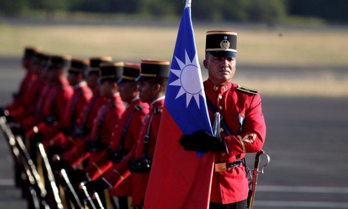 An honor guard holds a Taiwan flag before the arrival of Taiwan's President Tsai Ing-wen at the Oscar Arnulfo Romero International Airport in San Luis Talpa, El Salvador, on Jan. 12, 2017. (Jose Cabezas/Reuters)