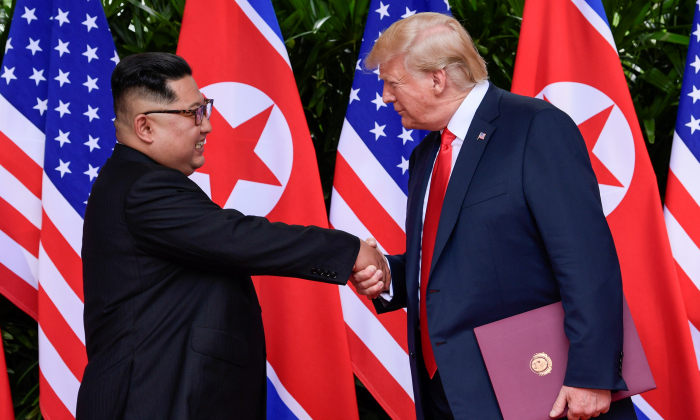 U.S. President Donald Trump and North Korea's leader Kim Jong Un shake hands during the signing of a document after their summit at the Capella Hotel on Sentosa island in Singapore June 12, 2018. (Susan Walsh/Pool via Reuters/File Photo)