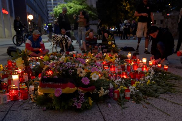 People lay flowers and light candles at the site of a fatal stabbing