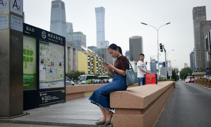 A woman uses her mobile phone at the entrance of an underpass in Beijing on September 18, 2018. (Wang Zhao/AFP/Getty Images)