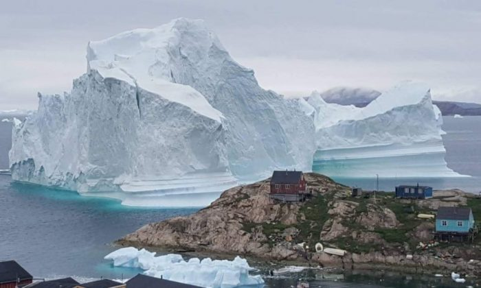 An iceberg behind houses and buildings after it grounded outside the village of Innarsuit, an island settlement in the Avannaata municipality in northwestern Greenland. (Magnus Kristensen/AFP/Getty Images)
