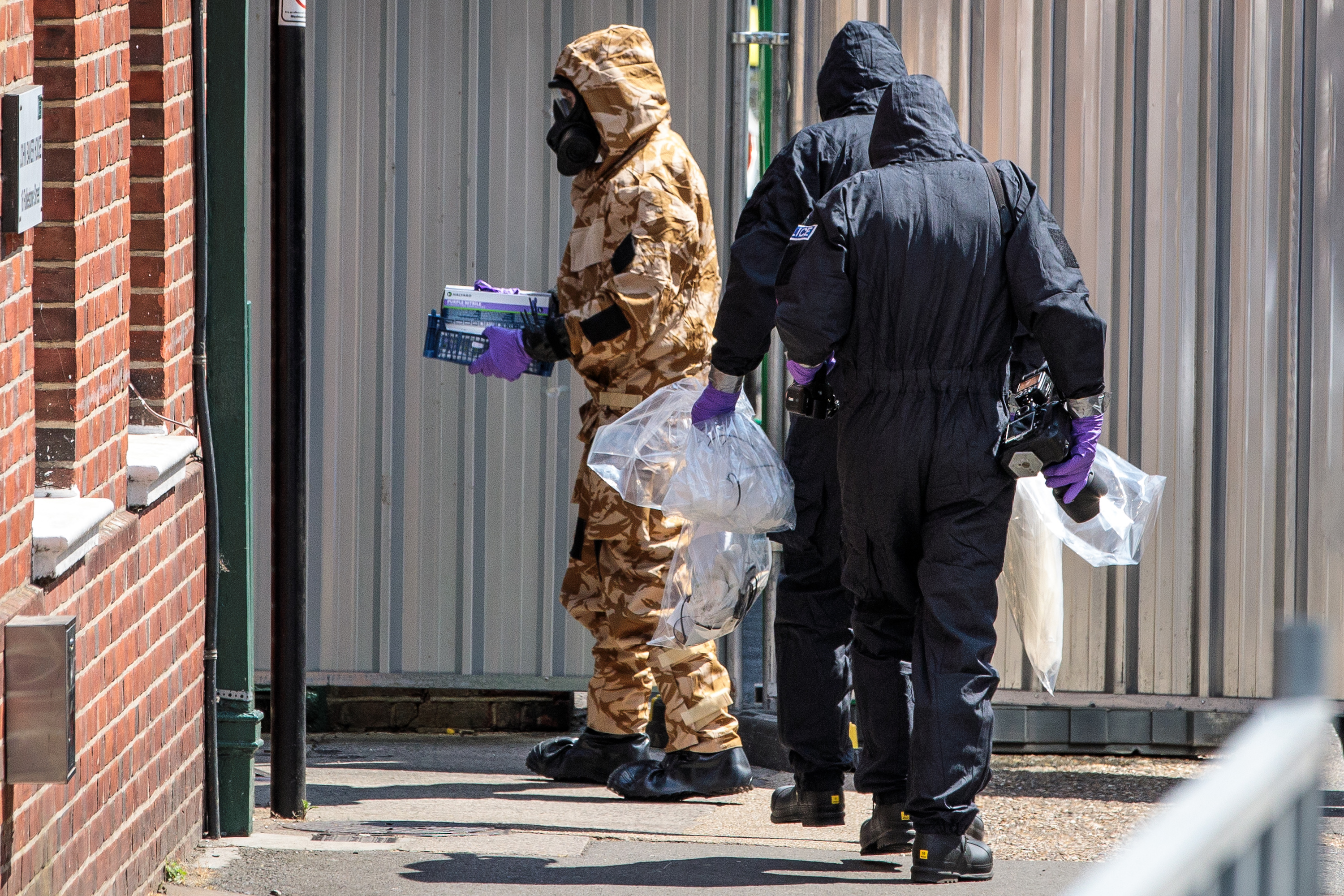 Workers in haz-mat suits search a residence