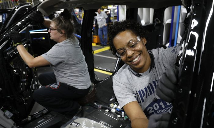 Ford workers Jasmine Powers (right) and Cassie Bell (left), both of Louisville, Kentucky, install visors into the 2018 Ford Expedition SUV as it goes through the assembly line at the Ford Kentucky Truck Plant in Louisville, Kentucky in Oct. 27, 2017. (Bill Pugliano/Getty Images)