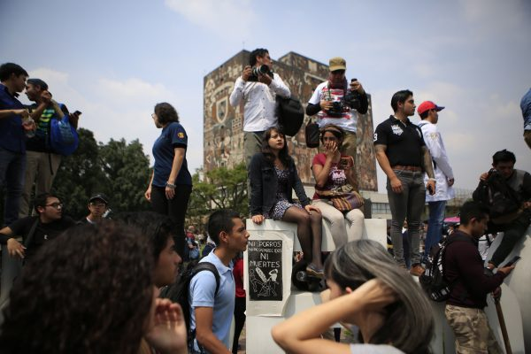 "People surround a sign reading in Spanish ""Neither porros, nor disappearances, nor murders; injustice,"" as thousands of students at Mexico's National Autonomous University protest to demand an end to violence by groups of thugs known as ""porros,"" who are often registered but don't attend classes, at the University's main campus in Mexico City, Wednesday, Sept. 5, 2018. Students at Mexico's largest university have gone on strike after a campus attack against protestors on Monday, in which two students were seriously injured. (AP Photo/Rebecca Blackwell)"