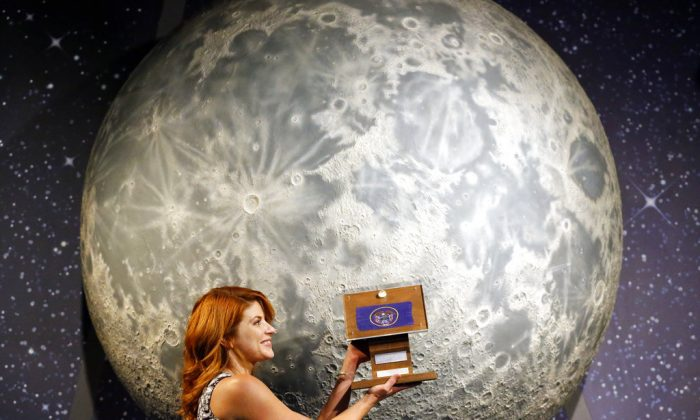 Lindsie Smith, from the Clark Planetarium, holds moon rocks encased in acrylic and mounted on a wooden plaque at the Clark Planetarium, in Salt Lake City, on Aug. 23, 2018. (AP Photo/Rick Bowmer)