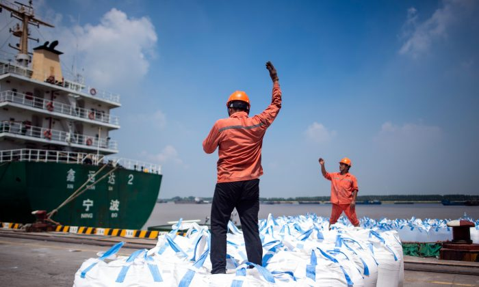 Workers unload bags of chemicals at a port in Zhangjiagang in eastern China's Jiangsu Province on Aug. 7, 2018. (JOHANNES EISELE/AFP/Getty Images)