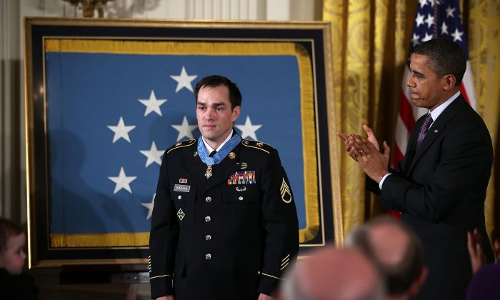 President Barack Obama (R) applauds after presenting the Medal of Honor for conspicuous gallantry to Clinton Romesha (L), a former Army Staff Sergeant, at the White House in Washington on Feb. 11, 2013. (Alex Wong/Getty Images)