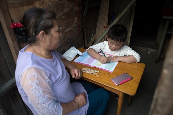 a woman helps a boy with his school homework inside their room in a migrant village on the outskirts of Beijing. Surrounded by the sleek hi-tech campuses and luxury condominiums of 'Beijing's Silicon Valley In this picture taken on Sept. 7, 2017,      (Photo credit should read NICOLAS ASFOURI/AFP/Getty Images)