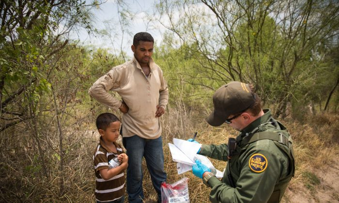 A Border Patrol agent takes down information of a man and his son who crossed the Rio Grande from Mexico into the United States in Hidalgo County, Texas, on May 26, 2017. (Benjamin Chasteen/The Epoch Times)