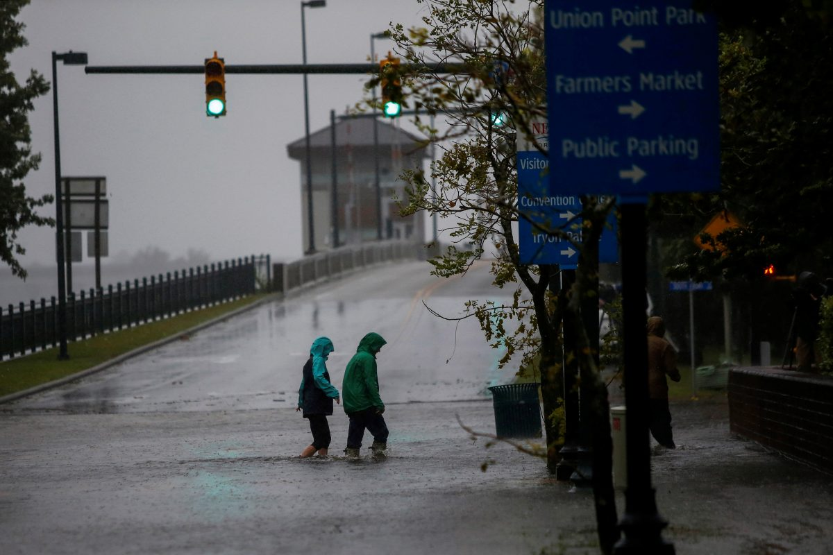 People walk along a flooded local street