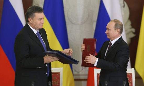 Russia's President Vladimir Putin (R) and his Ukrainian counterpart Viktor Yanukovych exchange documents at a signing ceremony after a meeting at the Kremlin in Moscow, Dec. 17, 2013. (Reuters/Sergei Karpukhin)