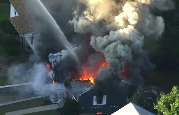 Flames consume the roof of a home in Lawrence
