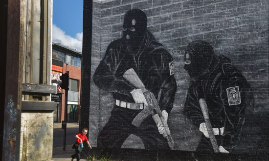 A young boy runs past a loyalist paramilitary mural in Belfast, Northern Ireland, on Oct. 13, 2015. (Charles McQuillan/Getty Images)
