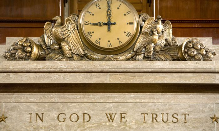 """A clock and the motto """"In God We Trust"""" over the Speaker's rostrum in the U.S. House of Representatives chamber in Washington, on Dec. 8, 2008.  (Brendan Hoffman/Getty Images)"""