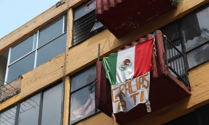 """A Mexican flag with a sign that says """"thanks to you"""" on Sept. 19, 2018 on a building in Multifamiliar Tlalpan, a housing development south of Mexico City, which sustained a lot of damage during the 2017 Mexico earthquake. (Tim MacFarlan/Special to The Epoch Times)"""