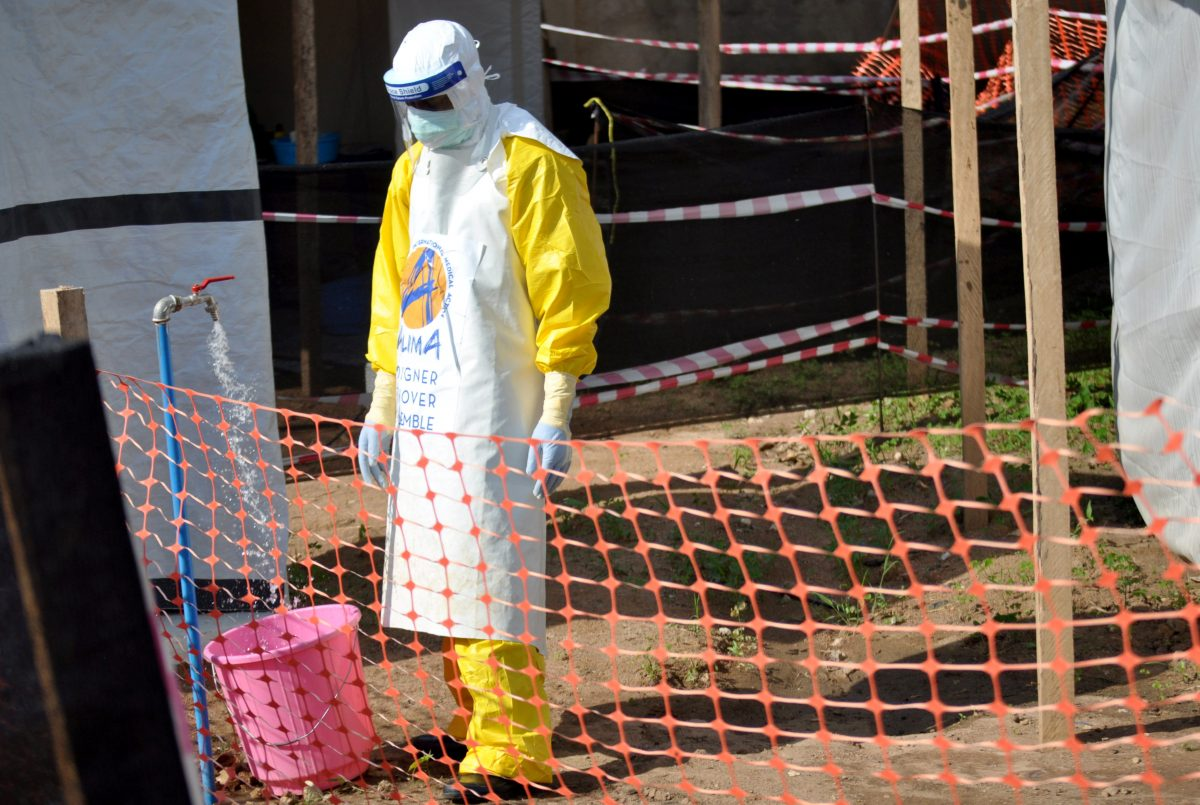 A medical worker wears a protective suit as he prepares to administer ebola patient care