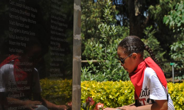 A young girl lays a rose at a memorial stone for the victims of the 2013 al-Shabaab attack on Westgate shopping mall in the Kenyan capital Nairobi on Sept. 20, 2015. (Tony Karumba/AFP/Getty Images)