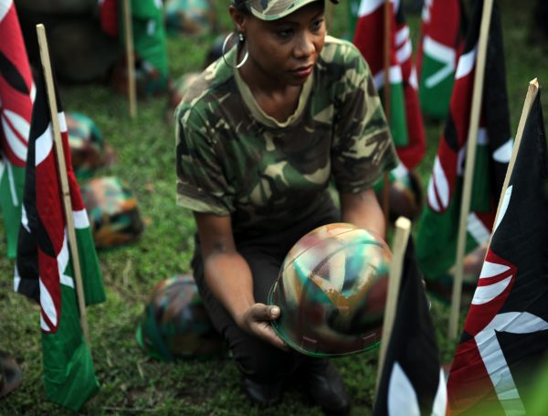 A woman holds a symbolic helmet among Kenyan flags at a vigil .