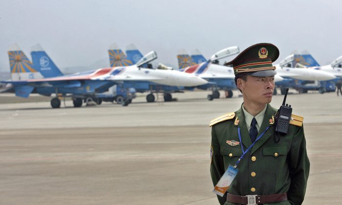 A Chinese paramilitary officer stands guard before a row of Russian Su-27 fighter jets ahead a rehearsal of aerobatics show at Zhangjiajie Lotus Airport in China's central province of Hunan, 17 March 2006. (LIU JIN/AFP/Getty Images)