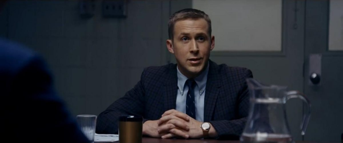 Ryan Gosling sitting at table with folded hands