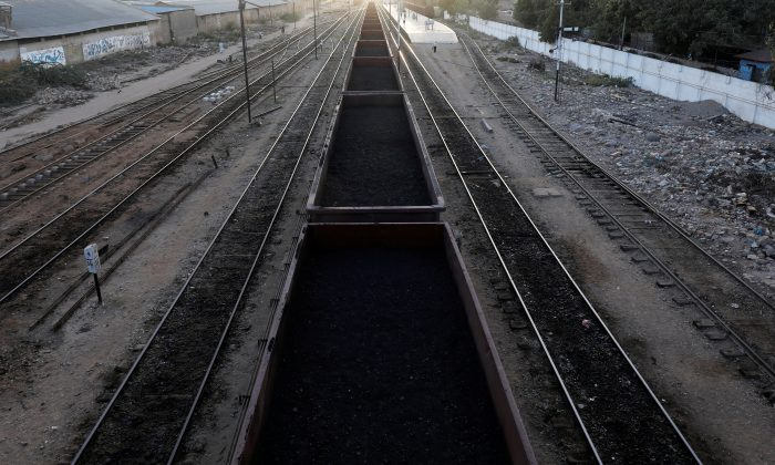 A cargo train loaded with coal dust moves past the port area near City Station in Karachi, Pakistan on Sept. 24, 2018. (Akhtar Soomro/Reuters)