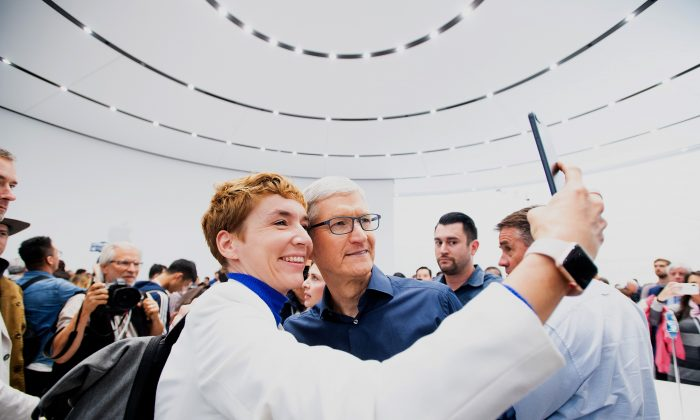 Apple CEO Tim Cook poses for a selfie with journalist Britta Weddeling during a launch event in Cupertino, California, on Sept. 12, 2018. (NOAH BERGER/AFP/Getty Images)