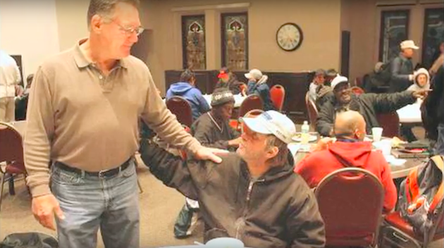 Bross greets someone at City Church breakfast.