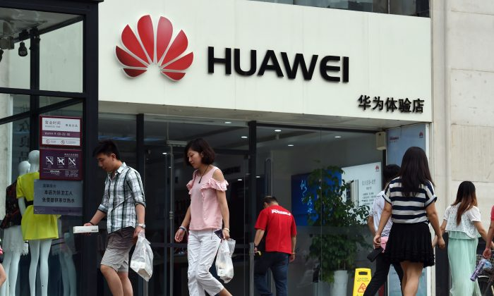 People walk past a Huawei store in Beijing on July 20, 2015. The Chinese telecoms equipment giant dominates the 5G wireless technology market, as part of Beijing's goals to achieve tech self-reliance. (Greg Baker/AFP/Getty Images)