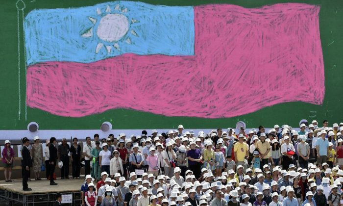 Overseas Taiwanese stand in front of a Taiwan flag while taking part in a National Day ceremony in Taipei on Oct. 10, 2017. (Sam Yeh/AFP/Getty Images)