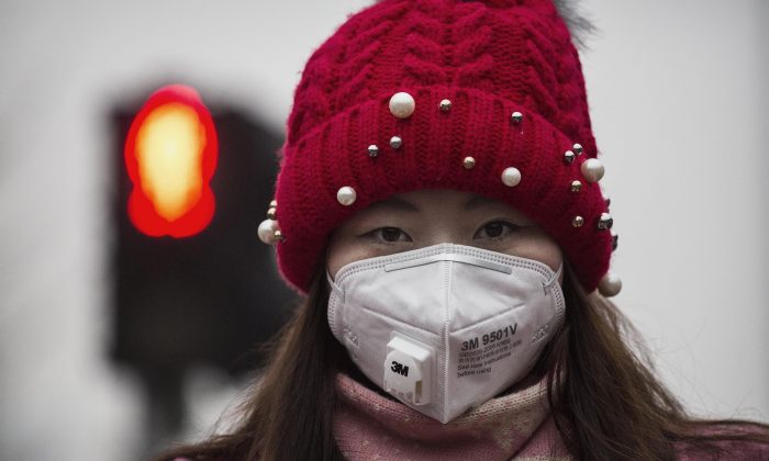 A woman wears a mask to protect against pollution as they wait to cross the street in heavy smog on Dec. 8, 2015 in Beijing, China. (Kevin Frayer/Getty Images)
