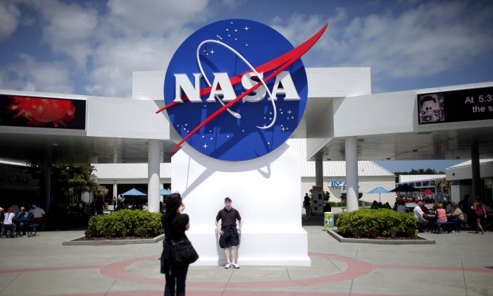 Tourists take pictures of a NASA sign at the Kennedy Space Center visitors complex in Cape Canaveral, Fla., on April 14, 2010. (Carlos Barria/Reuters)