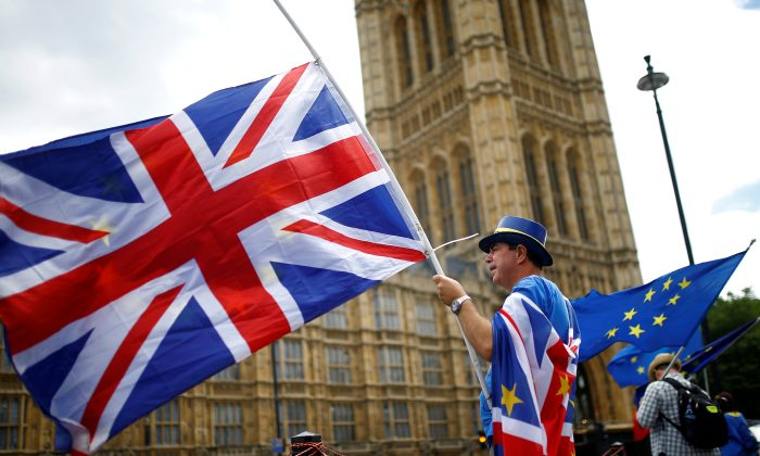 Anti-Brexit demonstrators wave EU and Union flags opposite the Houses of Parliament, in London on June 19, 2018. (Henry Nicholls/Reuters)