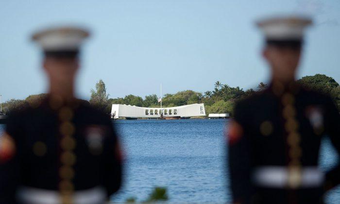 A U.S. Marine firing detail stands at attention with the Arizona Memorial in background during a memorial service on Dec. 7, 2011, for the 70th anniversary of the attack on the U.S. naval base at Pearl Harbor in 1941. (Kent Nishimura/Getty Images)