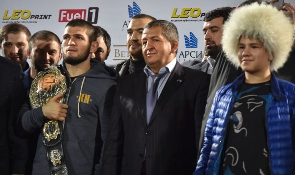 Khabib stands on stage with his father