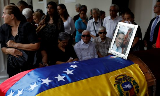 An image of the opposition lawmaker Fernando Alban and Jesus Christ is seen over his coffin during a ceremony at the National Assembly in Caracas, Venezuela, on Oct. 9, 2018. (Reuters/Marco Bello)