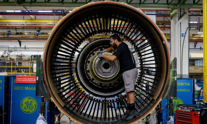 A man works with a jet engine at General Electric's aviation engine overhaul facility in Petropolis, Rio de Janeiro, Brazil on June 8, 2016. (YASUYOSHI CHIBA/AFP/Getty Images)