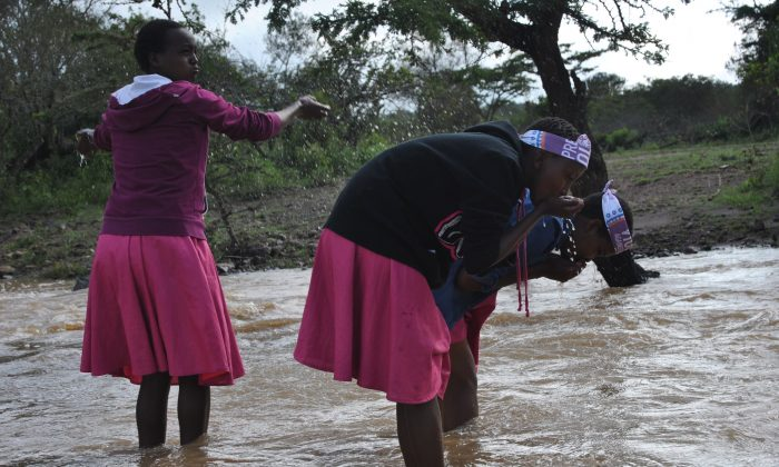 Girls who have taken refuge at the Samburu Girls Foundation drink water from a river near Loosuk, Samburu County, in north-central Kenya on June 6, 2018. (Dominic Kirui/Special to The Epoch Times)
