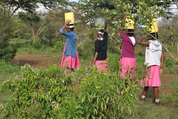 Girls who have taken refuge at the Samburu Girls Foundation carry buckets of water from a river.