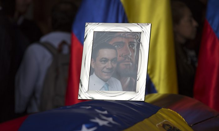 A framed portrait of opposition activist Fernando Alban shadowed by an image of Jesus Christ sits on the flag-draped casket containing his remains, during a solemn ceremony at the National Assembly headquarters, in Caracas, Venezuela, on Oct. 9, 2018. (Ariana Cubillos/AP)