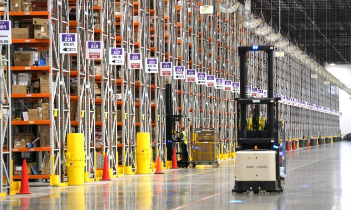 A worker drives a Powered Industrial Truck at the Amazon fullfillment center in Aurora, Colo., on May 3, 2018. (Rick T. Wilking/Getty Images)