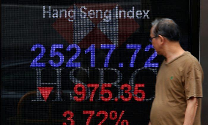 A man walks past a panel displaying the Hang Seng Index during morning trading in Hong Kong, China Oct. 11, 2018.  (Bobby Yip/Reuters)