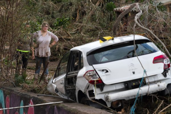 a resident looks at a damaged car