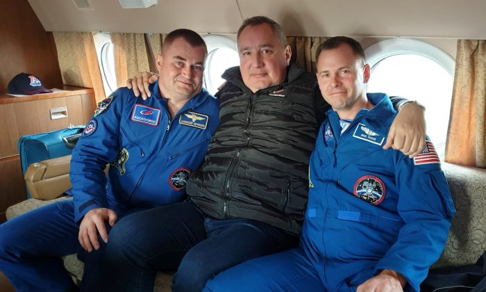 Head of Russian space agency Roscosmos Dmitry Rogozin (C) poses with astronauts Alexey Ovchinin of Russia and Nick Hague of the U.S., who survived the mid-air failure of a Russian rocket, on onboard a plane during a flight to Chkalovsky airport near Star City outside Moscow, Russia, on Oct. 12, 2018. (Russian space agency Roscosmos/Handout/Reuters)