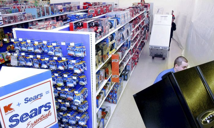 """FILE - In this March 24, 2005, file photo Kenmore refrigerators are wheeled into the existing K-Mart in Nashua, N.H., to become a """"Sears Essentials"""" store. Sears has filed for Chapter 11 bankruptcy protection Monday, Oct. 15, 2018, buckling under its massive debt load and staggering losses. (AP Photo/Jim Cole, File)"""
