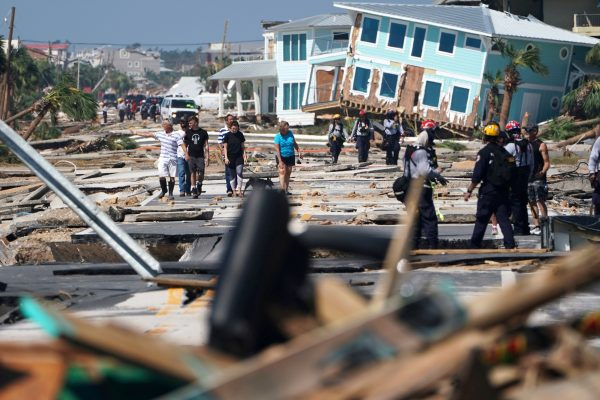 First responders and residents walk along a main street in Mexico Beach October 11