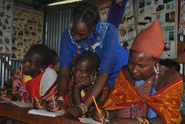 A teacher helps Naatana Karbolo with writing in a community school.