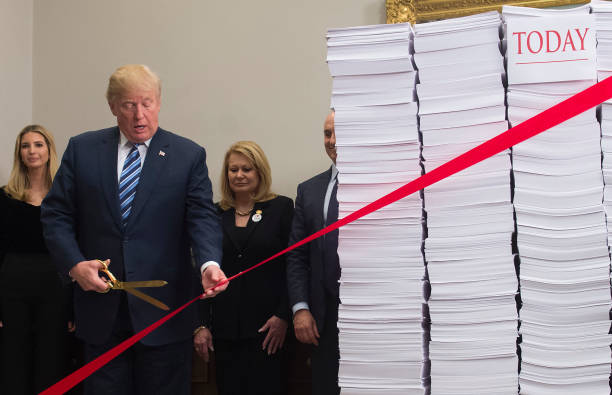 U.S. President Donald Trump holds gold scissors as he cuts a red tape tied between two stacks of papers representing the government regulations of the 1960s and the regulations of today (R) after he spoke about his administration's efforts in deregulation in the Roosevelt Room of the White House in Washington, DC, Dec. 14, 2017. (SAUL LOEB/AFP/Getty Images)
