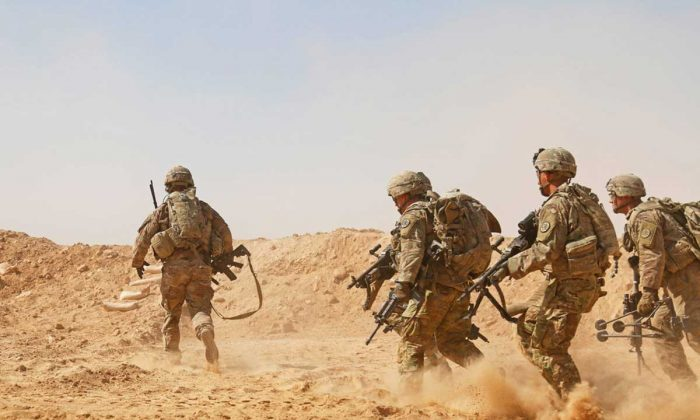 Soldiers rush to a berm to establish a hasty fighting position during a live-fire training exercise near Al Asad Air Base, Iraq, Sept. 26, 2018. (U.S. Army National Guard photo by 1st Lt. Leland White)