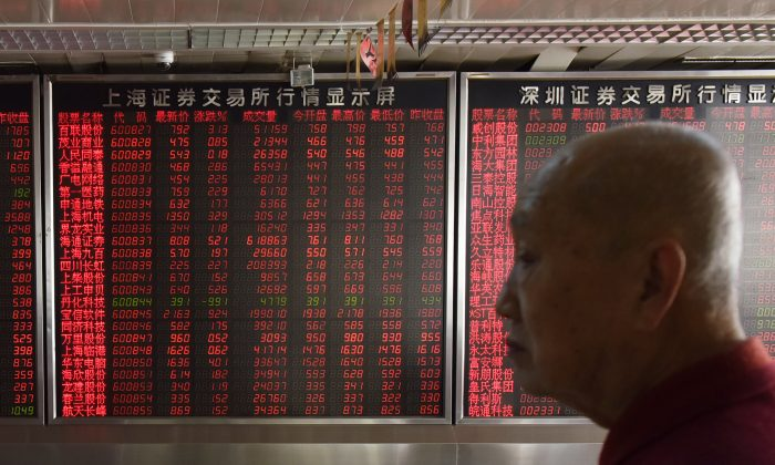 An investor stands in front of a screen showing stock prices at a securities company in Beijing on Oct. 19. (Greg Baker/AFP/Getty Images)